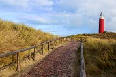 Brick Road To Lighthouse Texel On Blue Cloudy Sky Background Outdoors. National Park Duinen Van Texe poster