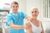 Elderly woman getting shoulder massage at physical therapy office poster