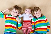 Two Happy Little Preschool Kids Boys With Newborn Baby Girl, Cute Sister. Siblings, Twins Children A poster