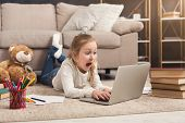 Shocked Little Casual Girl Watching Movie. Surprised Female Kid Lying On The Floor, Home Alone, Watc poster