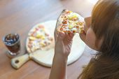 Woman Eating Tasty Pizza And Soft Drink In Restaurant. Top View. Young Girl Eating A Piece Of Delici poster