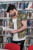 Bodybuilder Reading From Book In A Library poster