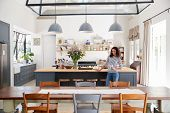 Mixed race woman leaning on kitchen island in open plan home poster