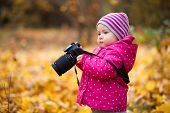 Little Kid Is Playing With Camera And Taking Photo Of Autumn Nature As Master. Baby Is In Autumn Par poster