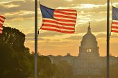 United States Capitol dome silhouette and the national flags of U.S.  rounding Washington Monument d poster