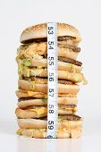 image of junk food  - A oversized burger with a tape measure around it