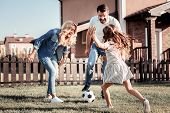 Play Together. Friendly Lovely Happy Family Having Fun Laughing And Playing Football Together On The poster