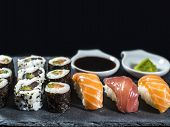 Close Up Sushi Set On Slate With Tuna And Salmon Sushis, Sushi Rolls And Wasabi On Black Background poster