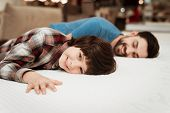 Handsome Bearded Father With Young Son Is Testing Mattress For Softness. Choosing Softness Of Mattre poster