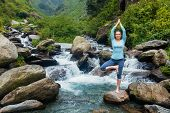 Woman in Hatha yoga balance yoga asana Vrikshasana tree pose at waterfall outdoors poster