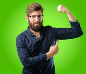 Young hipster man with big beard pointing biceps expressing strength and gym concept, healthy life i poster