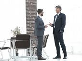 Two business executives talking about business in the office. poster