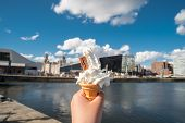Hand Holding Ice Cream Cone With Blurred Image Of The Building At Liverpool Waterfront Near Albert D poster