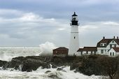 Huge Waves Crash Against Portland Head Lighthouse As Sunlight Breaks Through Storm Clouds. It Is The poster