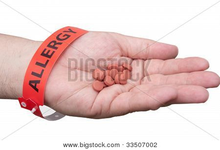 Hand With Allergy Wrist Band And Medicine