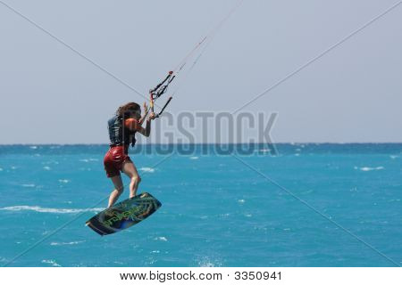 Kite Boarder Flying Through The Air On A Sunny Day