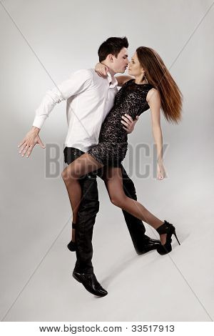 Beautiful Young Couple Are Dancing On Grey