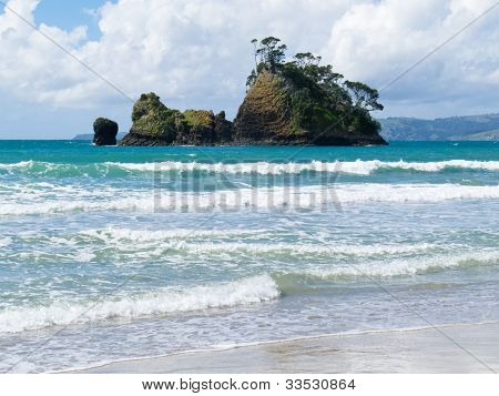 Small rocky island off sandy beach, Coromandel, NZ