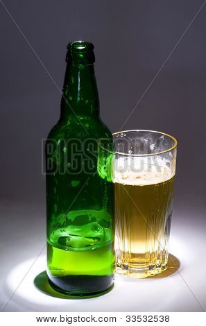 A bottle of beer, a glass of beer on the background of