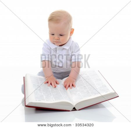 Little boy reads a big book