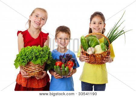 Smiling kids with fresh vegetables