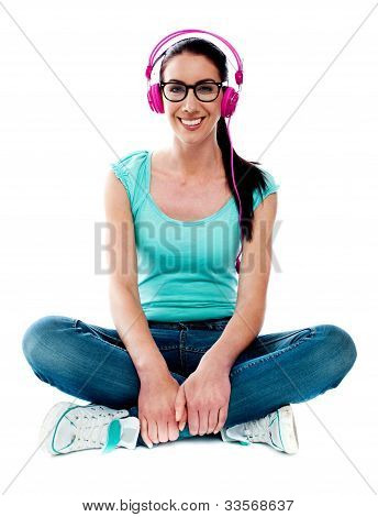 Teenager Sitting On Floor And Listening Music