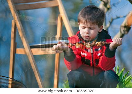 Four years old boy eats grilled vegetables