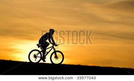 silhouette of a cyclist in sunrise