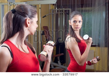 Beautiful young girl exercising with dumbbells