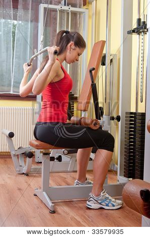 Beautiful girl exercising her back muscles in the gym