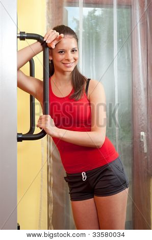 Beautiful smiling young woman standing beside leg workout machine in the gym