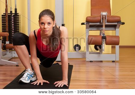 Beautiful young woman exercising in the gym on the floor