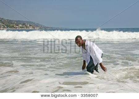 African American Man Running And Playing In The Surf
