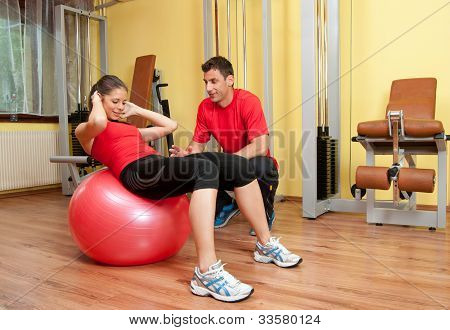 Beautiful young girl exercising abs in the gym under supervision of her coach