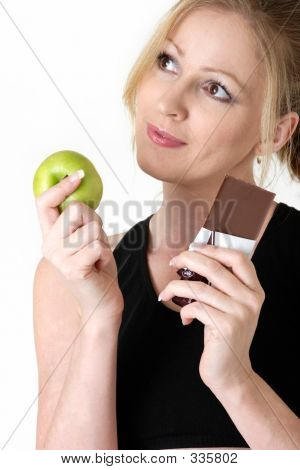 Woman Deciding Whether To Eat Apple Or Chocolate
