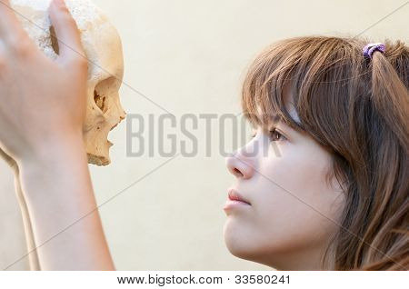 Teenage girl looking at human skull and thinking about life and death