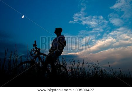 Silhouette of the man sitting on the bicycle at dusk and watching moon high in the sky