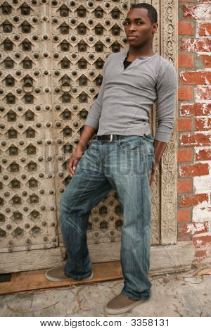 Sexy Young African American Man Leaning Against Grunge Background