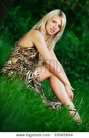 Portrait Of A Pretty Woman Sitting In The Grass