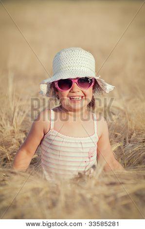Happy girl walking in the field of wheat