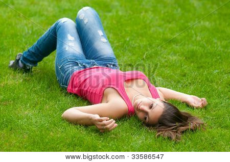 Beautiful girl lying on the grass on calm spring day