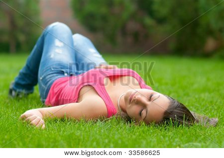 Beautiful girl lying on the grass on beautiful spring day