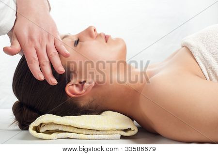 Beautiful young women getting a face massage in massage salon