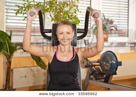 smiling beautiful young woman exercising in gym