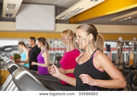 group of five people exercising in gym on treadmills