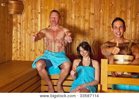 three people sitting in a sauna and posing thumbs up