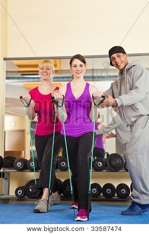 two young women exercising in gym with trainer