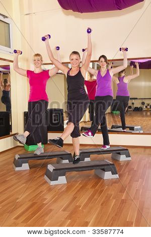 three smiling women performing aerobics exercises