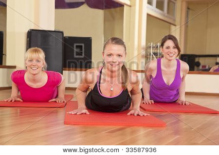 three young woman performing stretching exercise