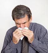 stock photo of rhinitis  - Closeup of mature man sneezing into a handkerchief suffering with nosebleed - JPG